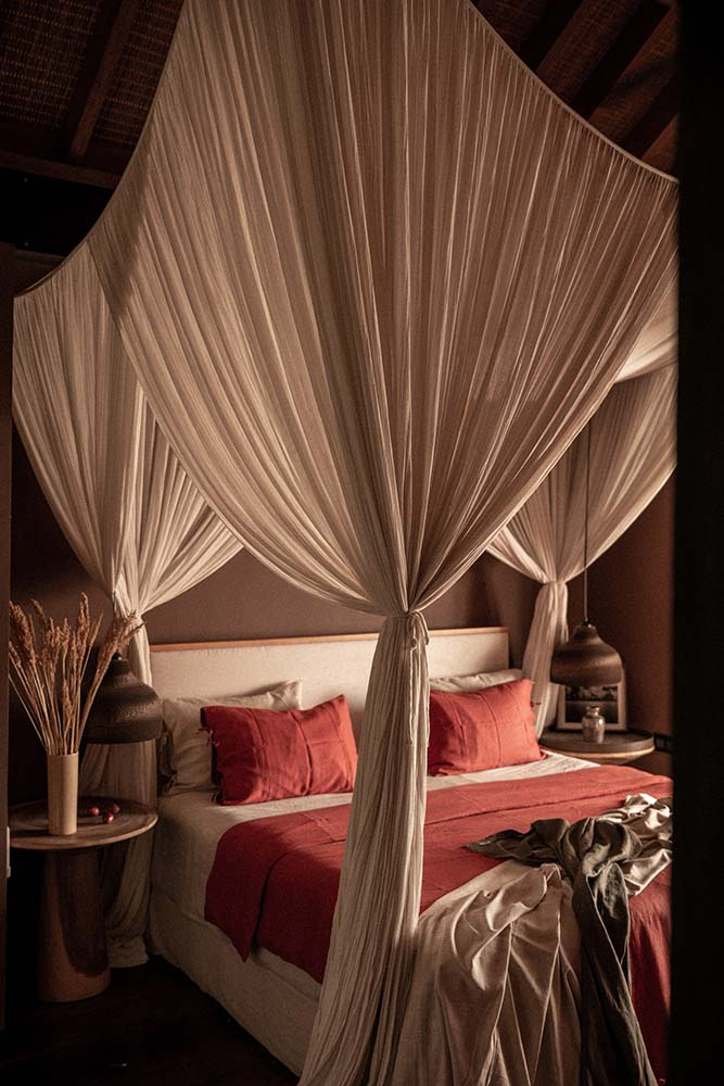 The bedroom has a four-poster bed flanked by bedside tables and surrounded by curtains.