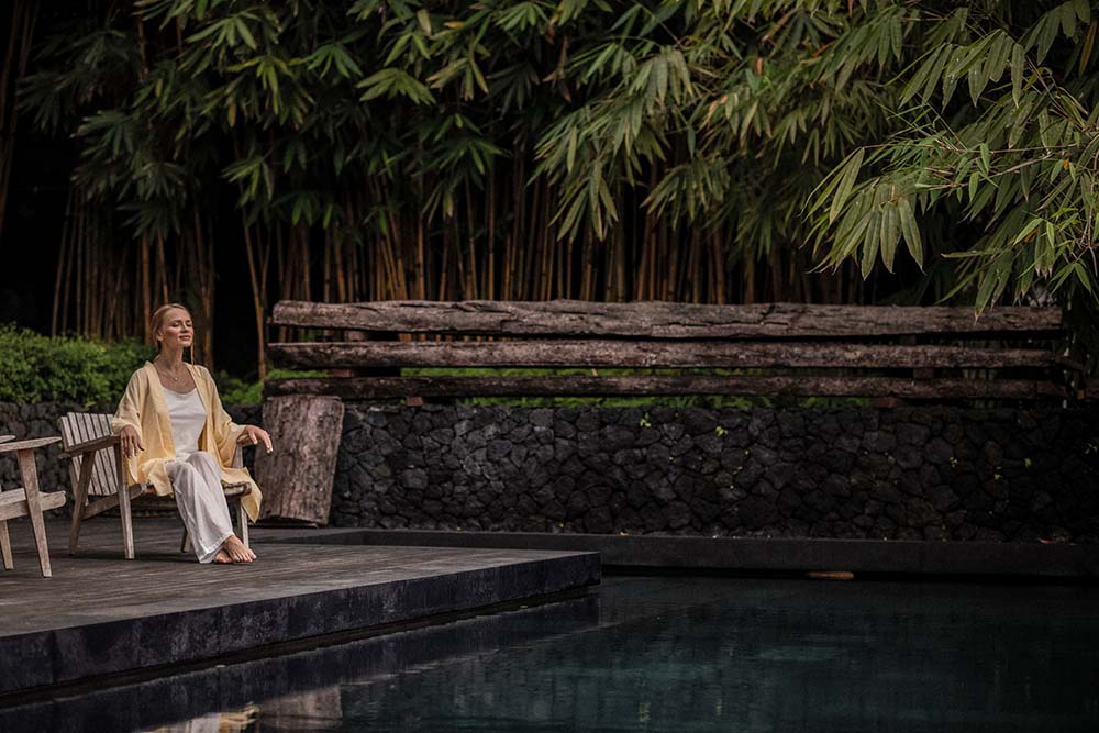 This is a close look at the pool area of the house adorned with tall trees and dark stones.
