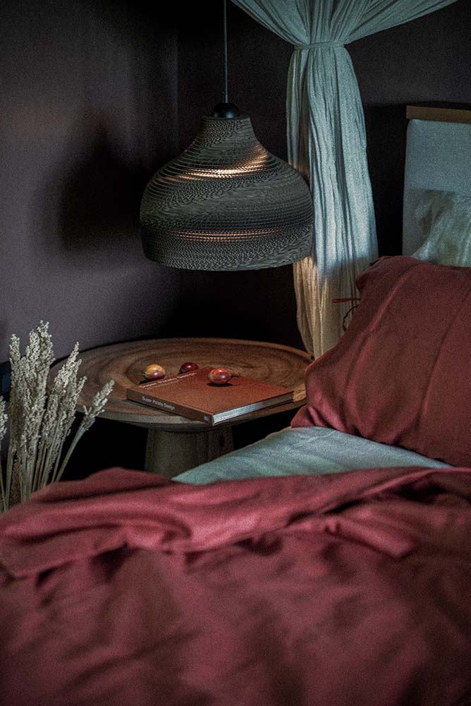 This is a close look at the round bedside table of the bedroom topped with a pendant light.