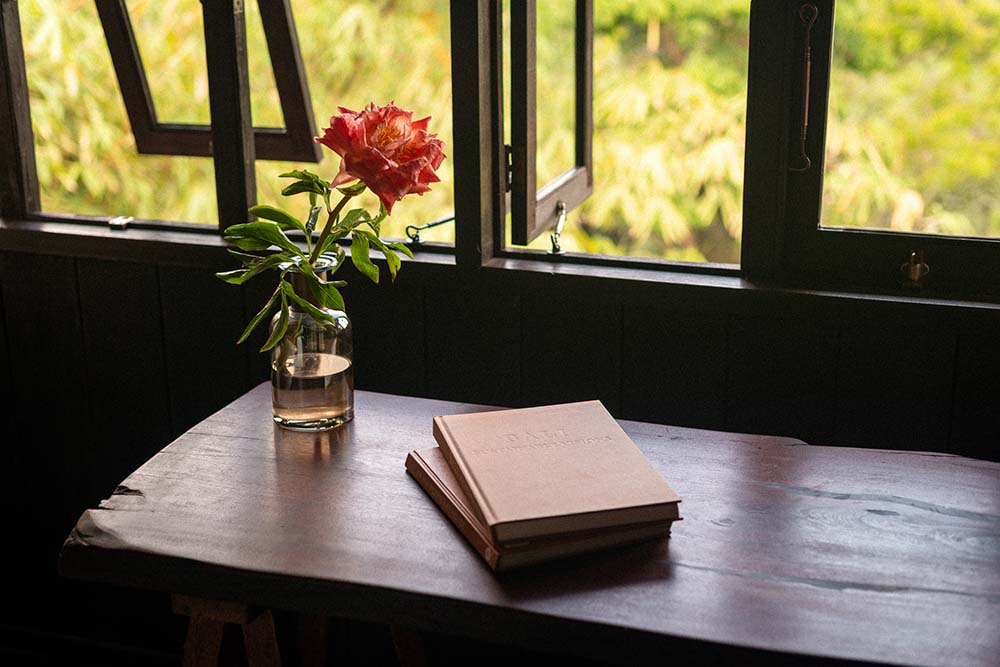 This is a close look at the wooden desk of the study area at the foot of the bedroom by the corner window.