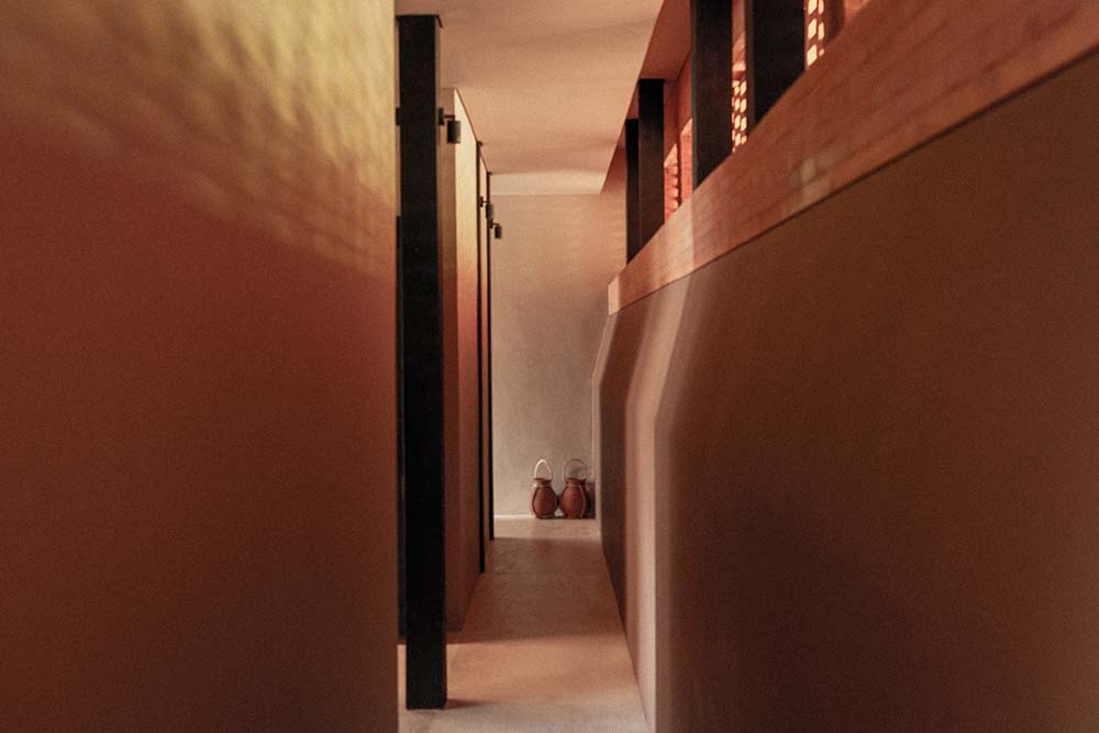 This is a close looka t the narrow hallway of the house with dark brown walls and warm lighting.