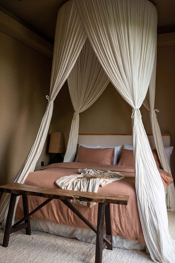 This is a close look at the bedroom with a large bed topped with curtains and has a rustic wooden bench at the foot.