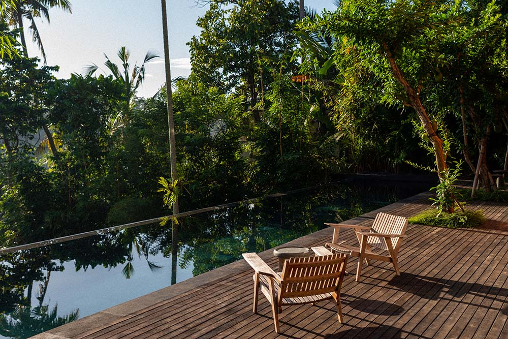 This is a close look at the infinity pool with a wooden deck flooring on the side fitted with armchairs facing the view of the treetops.