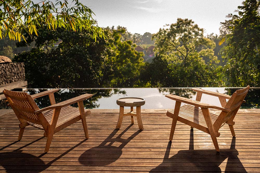 This is the view of the treetops and landscape from the vantage of the poolside that has a couple of wooden armchairs.