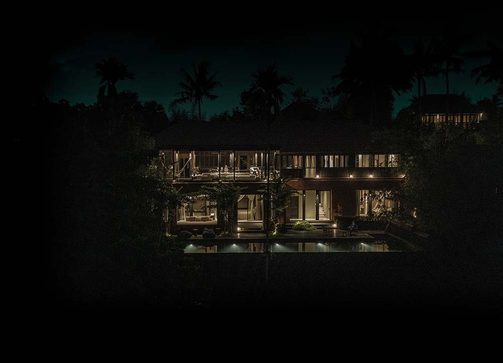 This is a far view of the house during nighttime to show the warm glow of the windows and glass walls of the house.