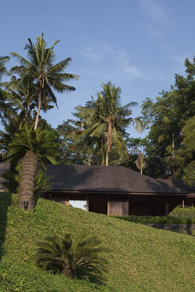 The grass lawn has small hills and tropical trees and shrubs that pair well with the earthy exterior walls of the house.