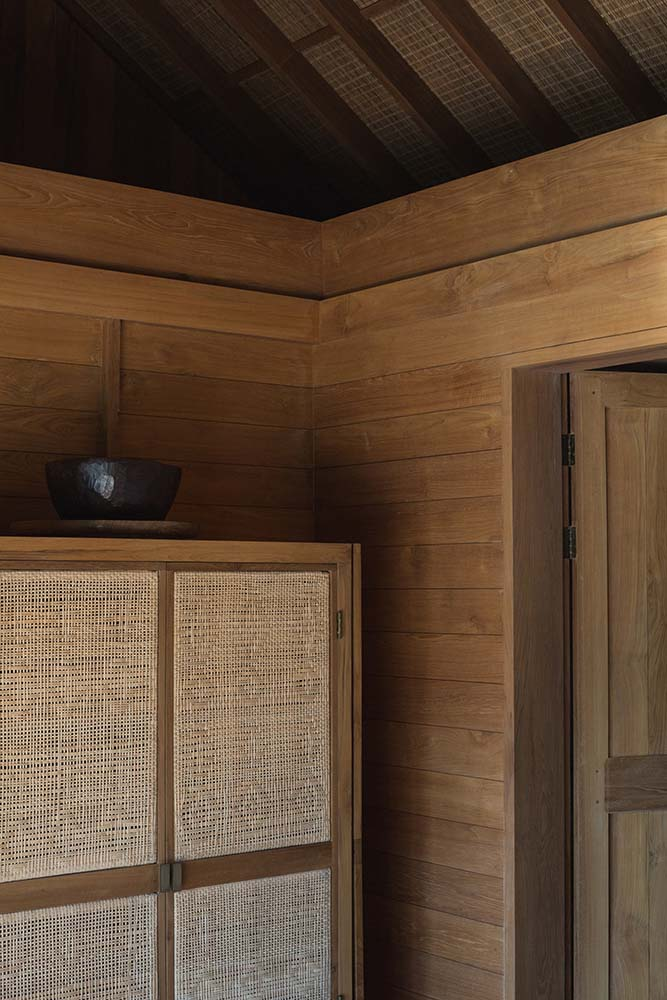 On the side of the bed is the large wooden cabinet and dresser with rustic woven elements to its cabinet doors.