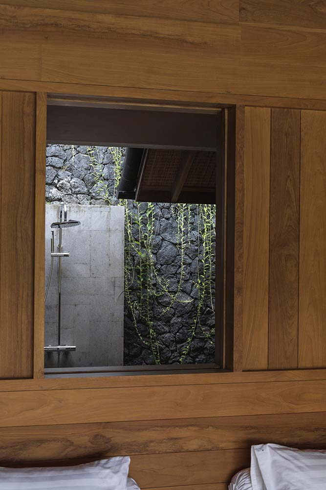 This is a wooden window above the headboard of the bed with a view of the shower area with mosaic textured stone wall and creeping vines.