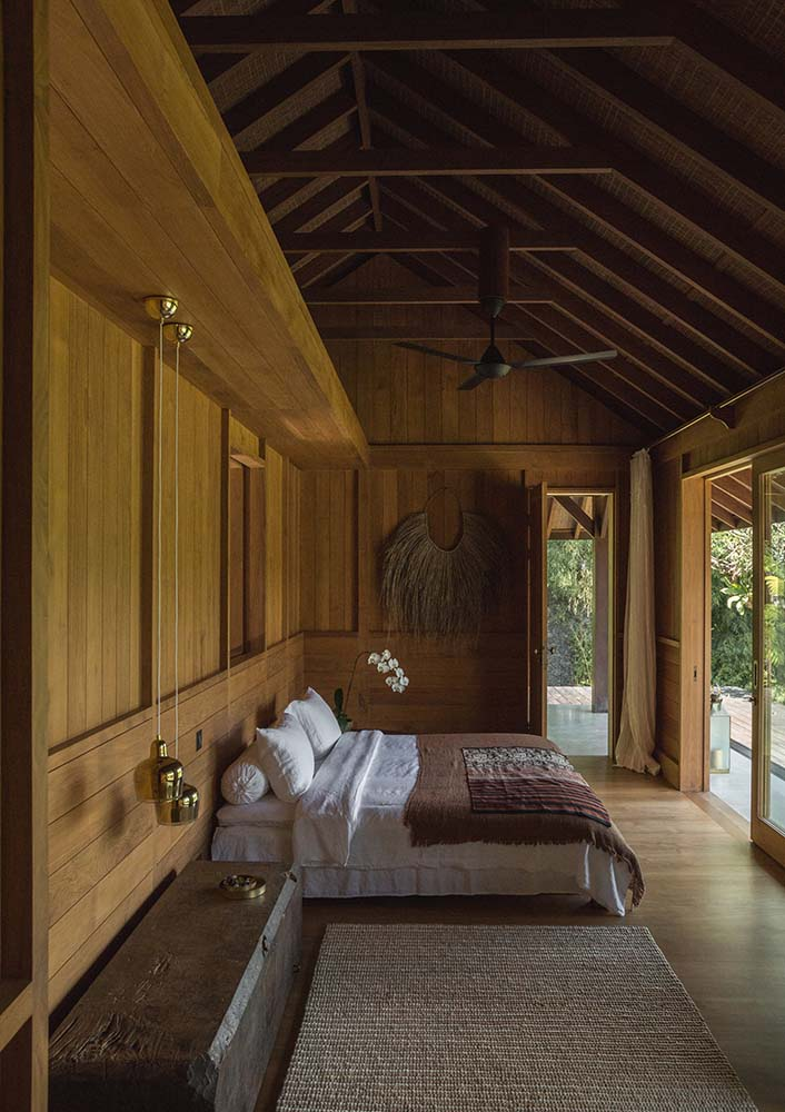 This bedroom has a platform bed topped iwth a tall beamed wooden cathedral ceiling that has a ceiling fan.