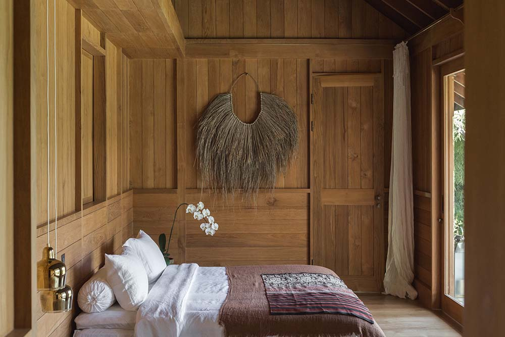 The bed stands out against the surrounding wooden elements and walls adorned with a wall-mounted rustic artwork on the far wall.