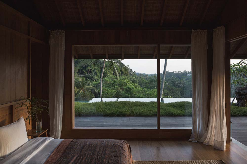 On the side of the bedroom is a large glass wall that lets in natural lighting as well as provide a view of the surrounding landscape of green grass and tropical trees.