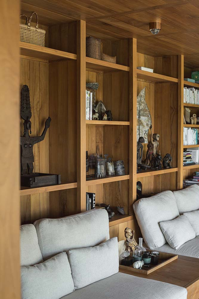 This is a close look at the den with built-in cushioned benches paired with built-in wooden shelves filled with various decors and displays.