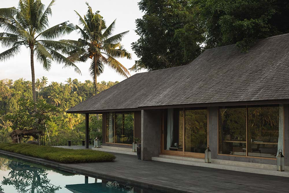 This is another look at the poolside area of the house with a view of the glass walls and earthy roofs complemented by the tall tropical trees.