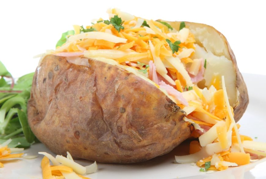 This is a close look at a taco stuffed baked potato on a white plate.