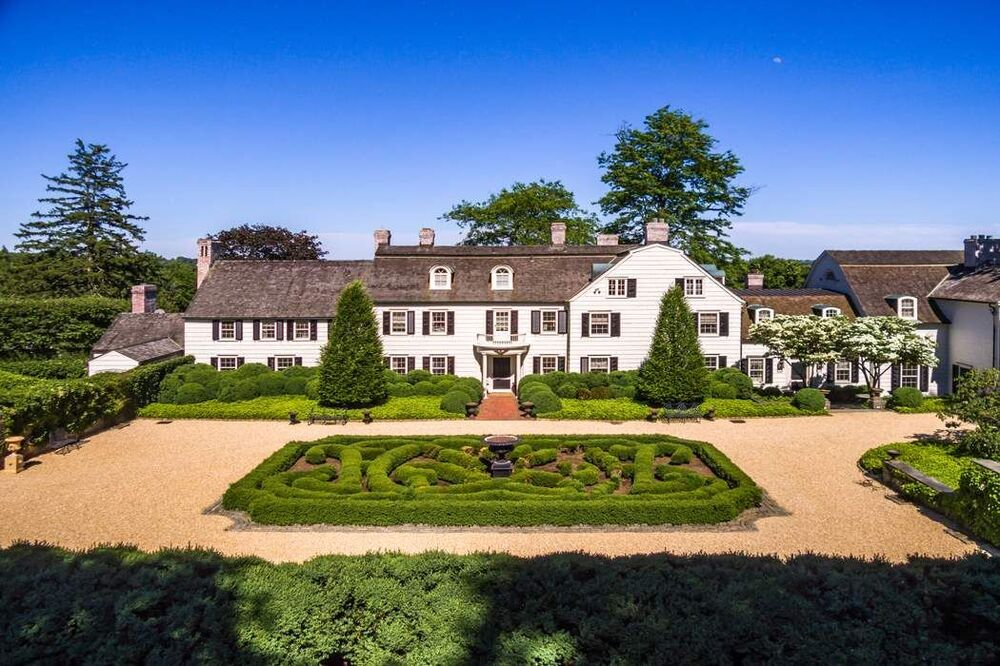 This is an aerial view of the front of the main house that has a large garden maze in front along with trees and shrubs to complement the bright exterior walls.