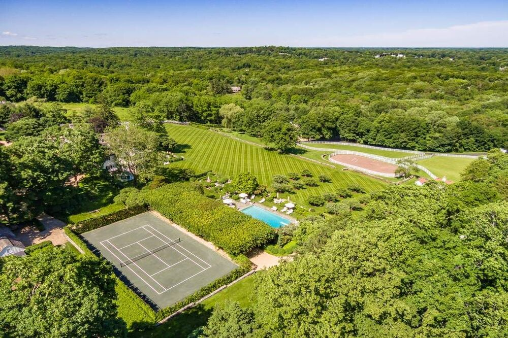 This is an aerial view of the tennis court and its proximity to the riding ring. These are then complemented by the lush landscaping. Image courtesy of Toptenrealestatedeals.com.