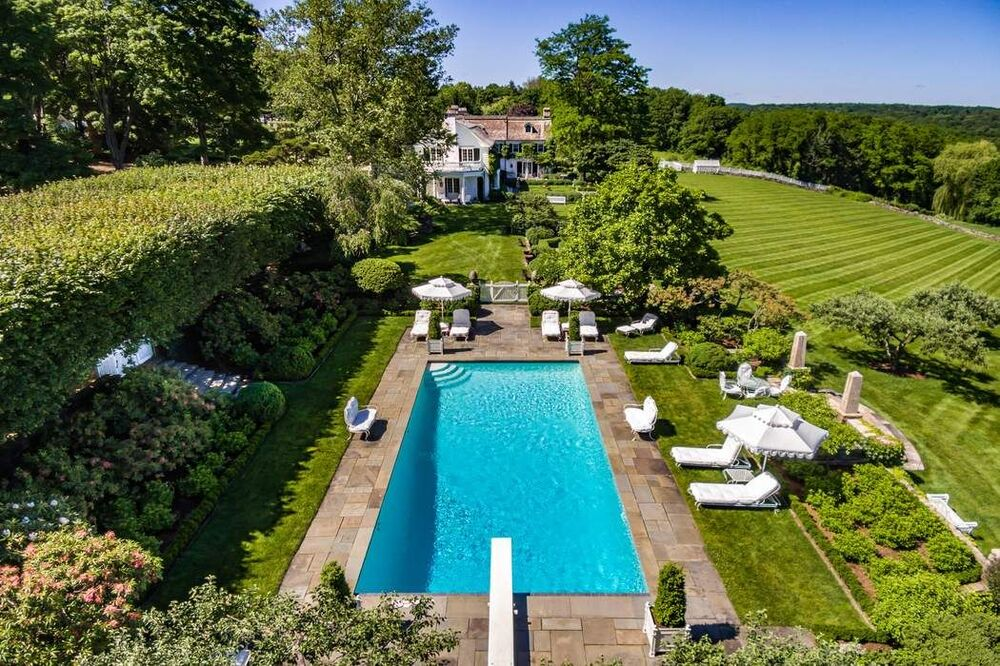 This is an aerial view of the poolside area surrounded by various lounge areas and thick shrubs. Image courtesy of Toptenrealestatedeals.com.