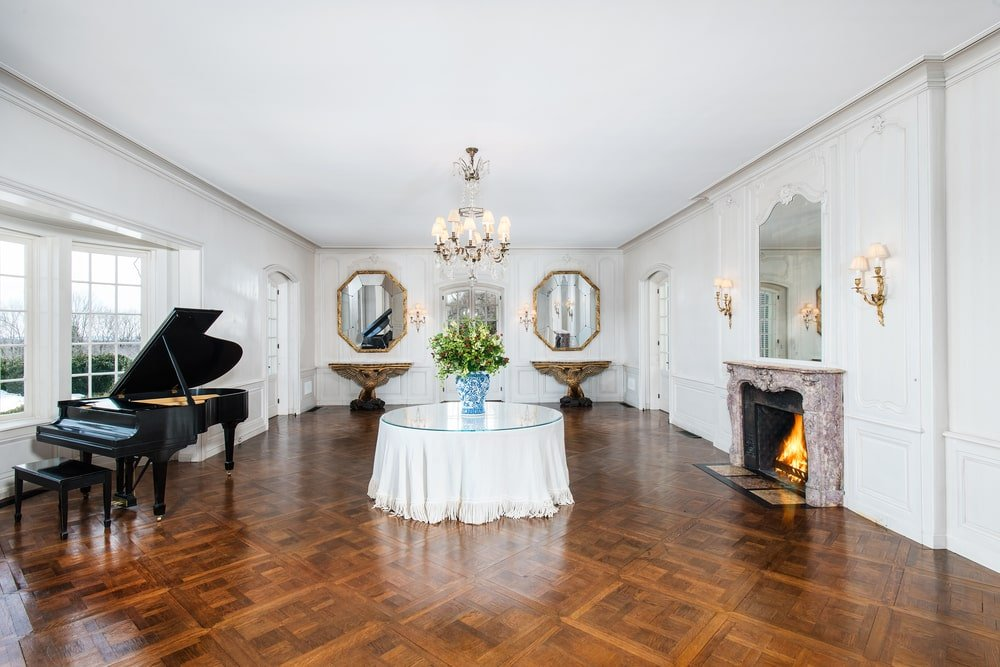This is the large ballroom that has a patterned dark hardwood flooring, a grand piano and a large fireplace on the other side. Image courtesy of Toptenrealestatedeals.com.