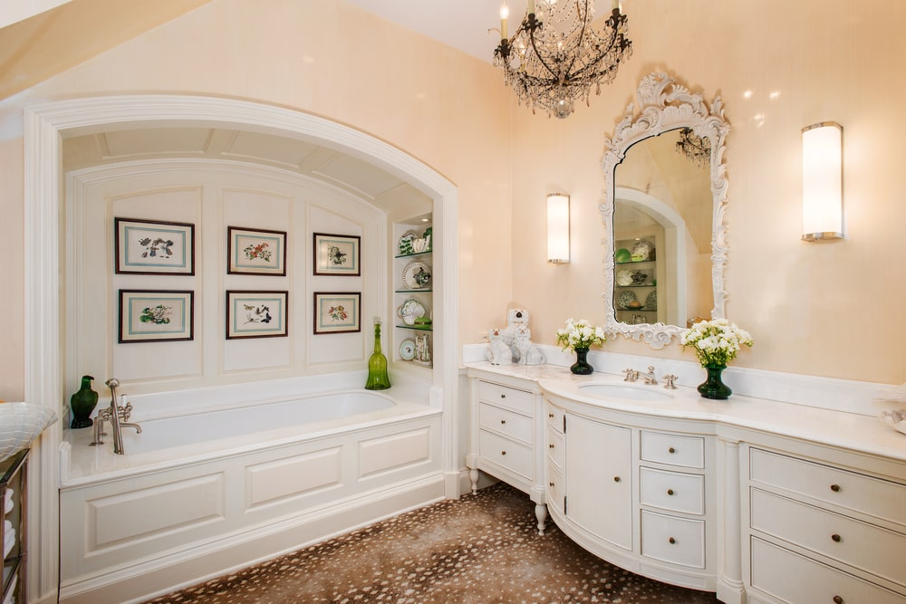 The primary bathroom has a large white bathtub embedded into its own alcove by the white vanity topped with a chandelier. Image courtesy of Toptenrealestatedeals.com.