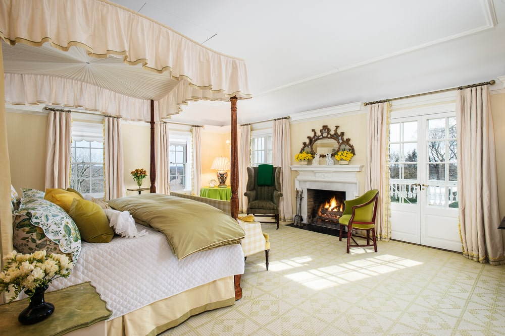 The primary bedroom has a large wooden four-poster bed across from the large white-mantel fireplace that complements the light pink walls brightened by white French windows. Image courtesy of Toptenrealestatedeals.com.