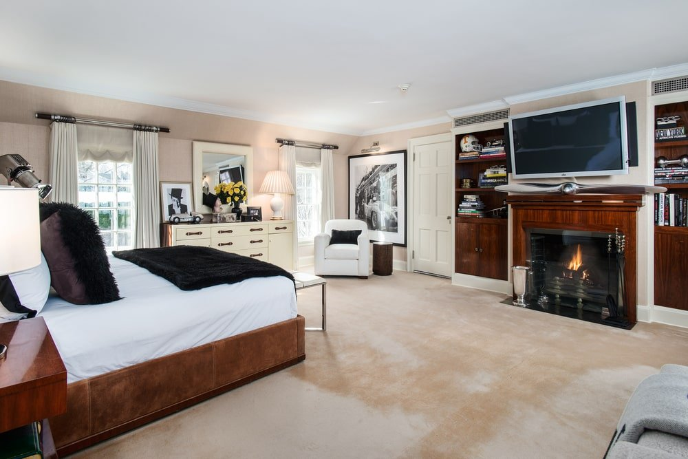This other bedroom has a dark platform bed that matches well with the mantel of the fireplace and the built-in bookshelves that stand out against the beige walls. Image courtesy of Toptenrealestatedeals.com.
