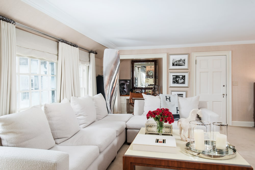 On the side of one of the bedrooms is a large L-shaped sectional sofa paired with a large wooden coffee table by the window. Image courtesy of Toptenrealestatedeals.com.