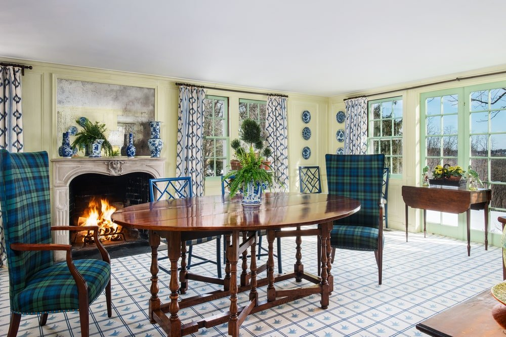 This is the informal dining room and breakfast nook with a small wooden dining table and green chairs by the large fireplace on a patterned area rug. Image courtesy of Toptenrealestatedeals.com.