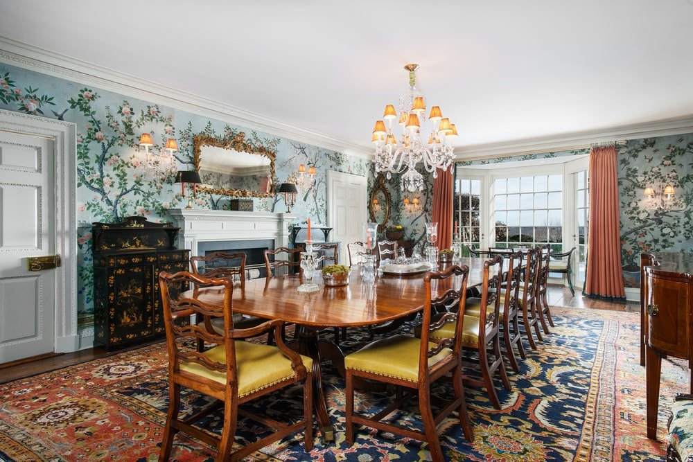 This is the formal dining room that has a large wooden dining table surrounded by matching wooden chairs, topped iwth a crystal chandelier and warmed by a fireplace. Image courtesy of Toptenrealestatedeals.com.