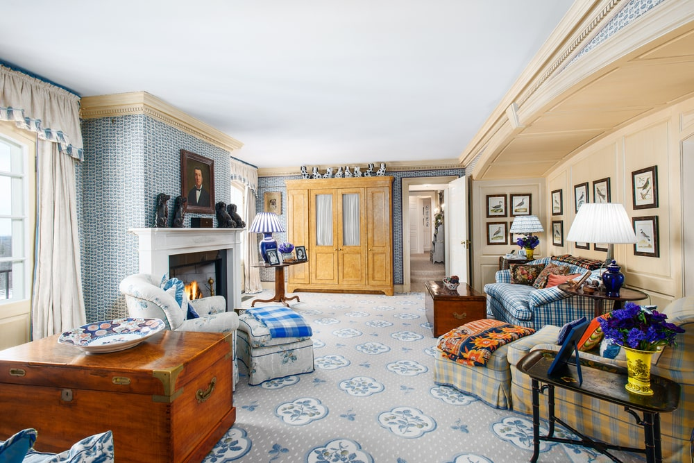 This is the comfortable and spacious family room with patterned carpeting and comfortable sofas across form the white fireplace. Image courtesy of Toptenrealestatedeals.com.
