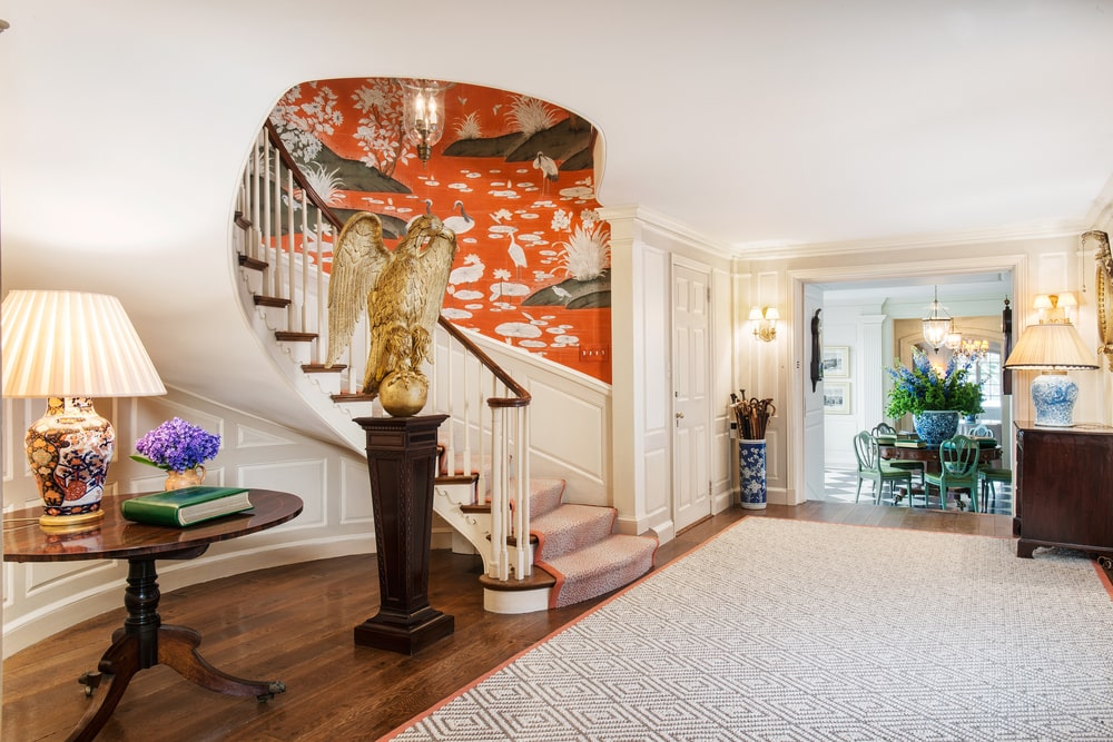 This is the foyer that has a large gray area rug on the dark hardwood flooring that matches the dark wooden table and pedestal on the side of the staircase. Image courtesy of Toptenrealestatedeals.com.