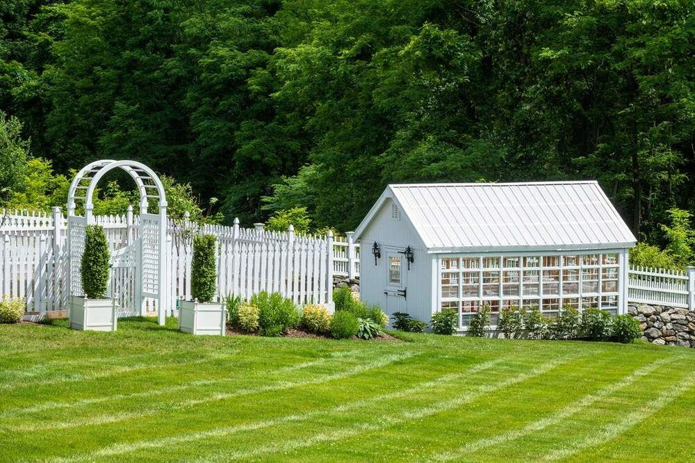 This is the greenhouse with white exteriors that match the white fencing of the vegetable garden beside it. Image courtesy of Toptenrealestatedeals.com.