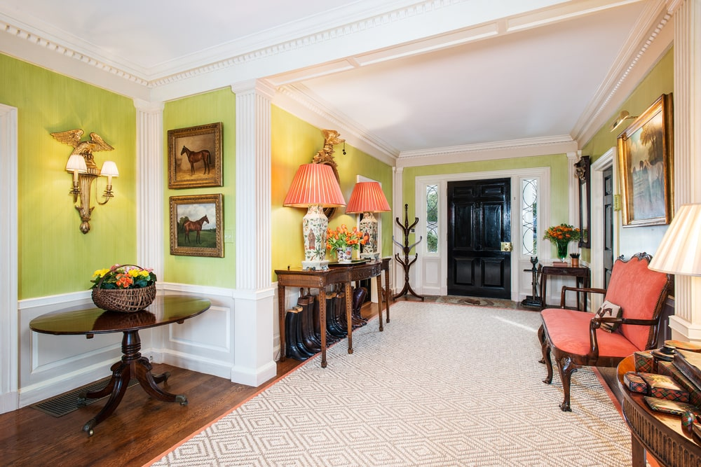 This is the foyer of one of the guesthouses with neon yellow walls and white wainscoting to contrast the dark brown furniture. Image courtesy of Toptenrealestatedeals.com.
