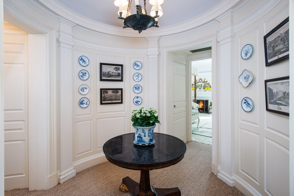 This is the foyer inside one of the guesthouses with a large curved light beige walls that contrast the dark round wooden table topped with a simple a chandelier. Image courtesy of Toptenrealestatedeals.com.