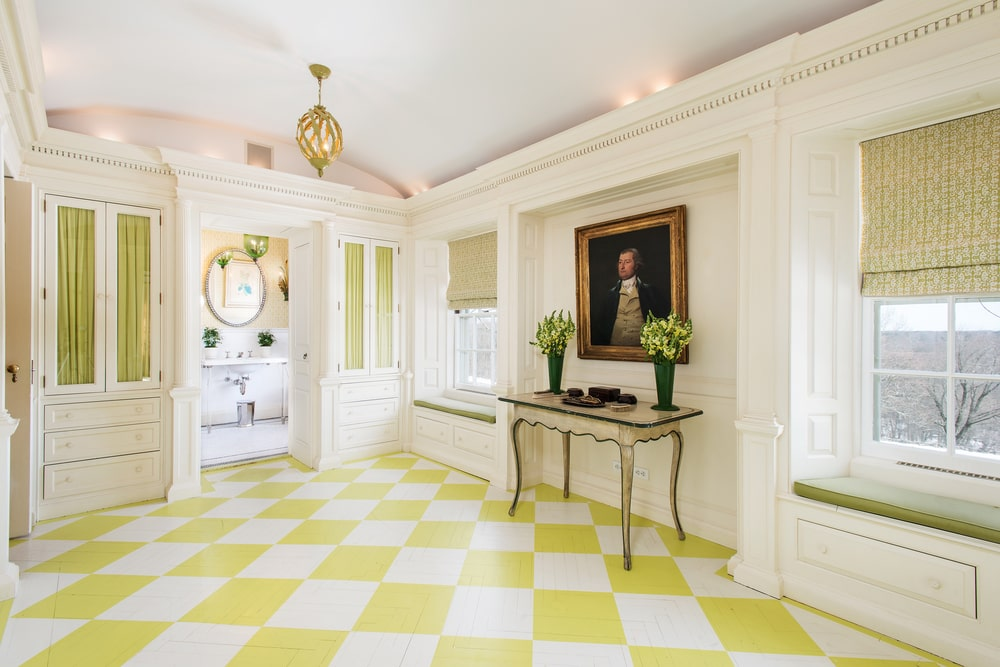 This is a large hallway leading to the bathroom with a console table on the side topped with a wall artwork complemented by the yellow checkered floor. Image courtesy of Toptenrealestatedeals.com.
