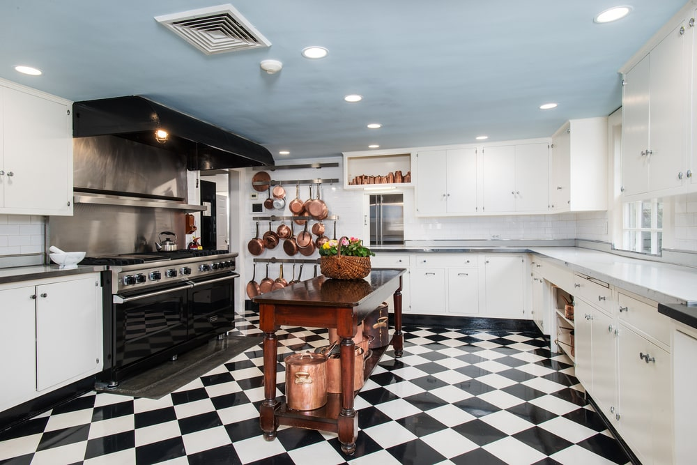 This is a close look at the kitchen that has a wooden kitchen island in the middle of a checkered black and white floor across the large black stove-top oven. Image courtesy of Toptenrealestatedeals.com.