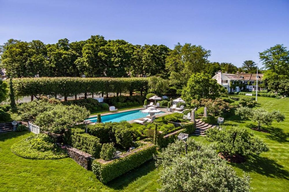 This is a look at the landscaping of the back of the house with lush shrubs and tall trees surrounding the large swimming pool. Image courtesy of Toptenrealestatedeals.com.