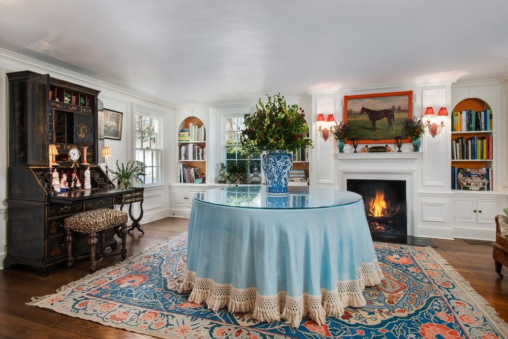 This is the library that has a white fireplace and a study desk along with built-in bookshelves and a large display table in the middle of a large patterned area rug. Image courtesy of Toptenrealestatedeals.com.