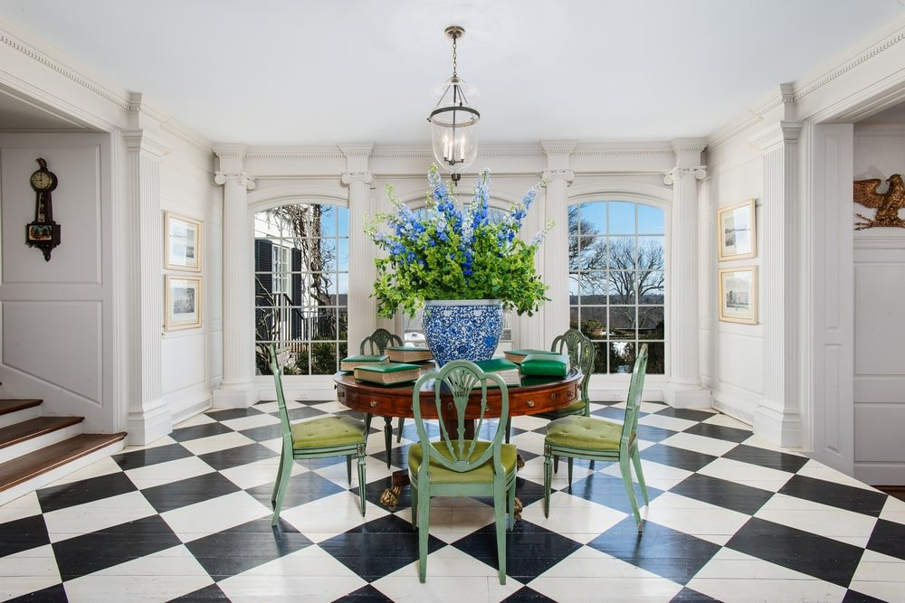 This is a close look at the study area of the library with a wooden round table and green chairs on a checkered floor. Image courtesy of Toptenrealestatedeals.com.