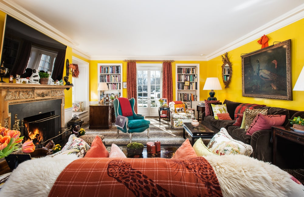 This is the large and bright living room with a white ceiling, yellow walls and a fireplace across from the sofa set and dark coffee table. Image courtesy of Toptenrealestatedeals.com.