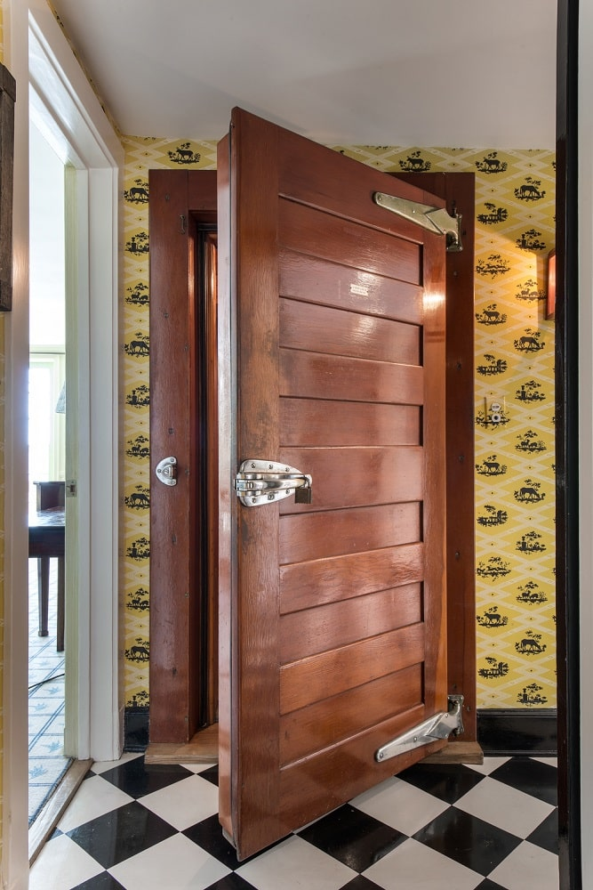 This is a close look at the vintage door of the meat locker within the house adorned with yellow wallpaper. Image courtesy of Toptenrealestatedeals.com.