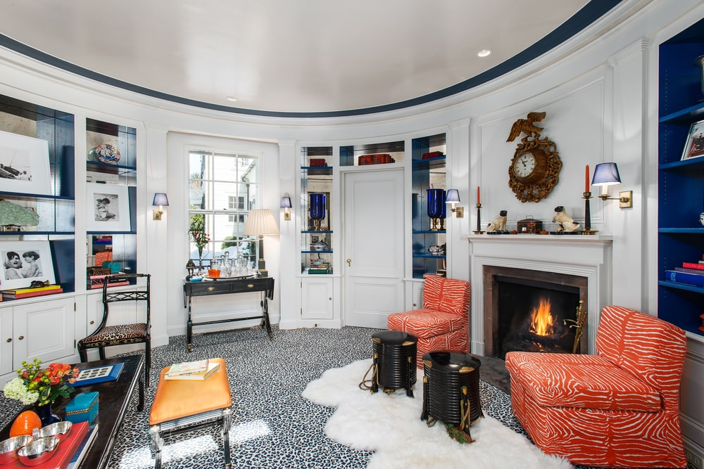 This is a close look at the home office and den that has white curved walls adorned by decors and bookshelves along with a fireplace. Image courtesy of Toptenrealestatedeals.com.