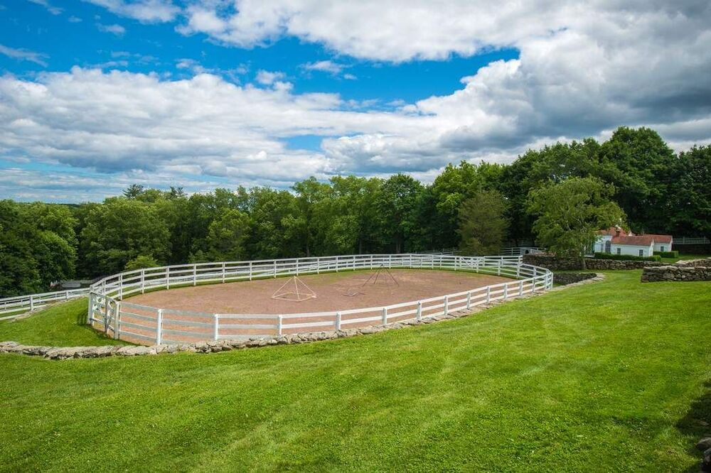 This is an aerial view of the large outdoor riding ring that has sand and white fences and has a background of tall trees. Image courtesy of Toptenrealestatedeals.com.