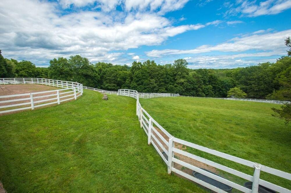 This is a closer view of the side of the riding ring with another layer of white fences. Image courtesy of Toptenrealestatedeals.com.