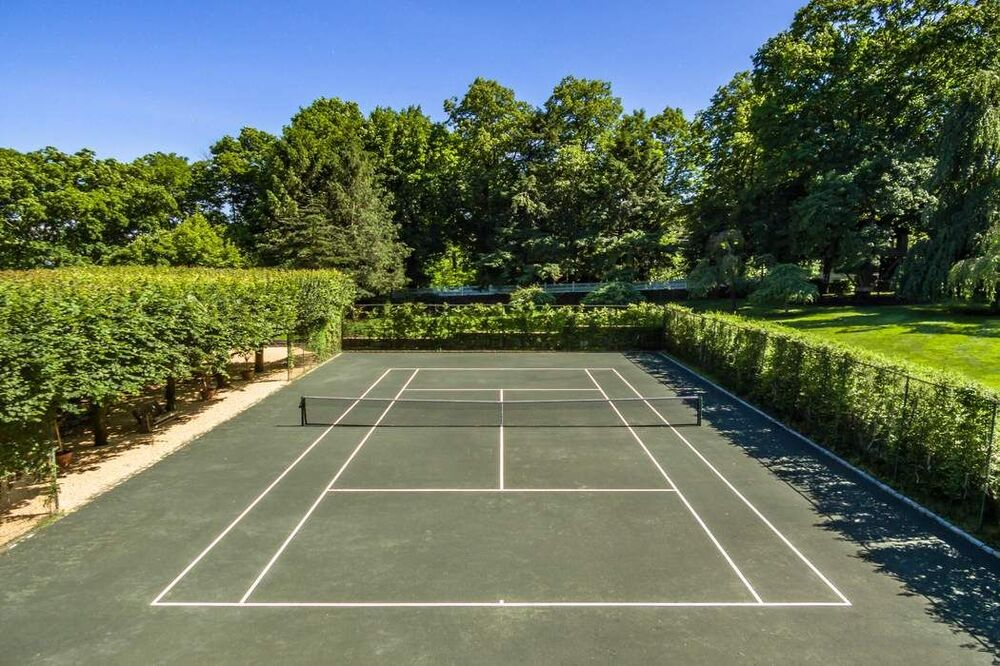 This is a close look at the tennis court that has a green tone surrounded by tall shrub hedges and tall trees in the background. Image courtesy of Toptenrealestatedeals.com.