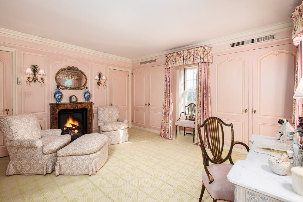 This is a look at the vanity room with pink walls and a lounge area by the fireplace across from the vanity. Image courtesy of Toptenrealestatedeals.com.