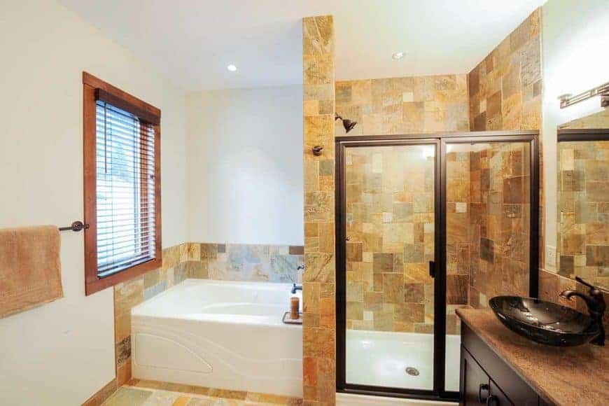 This is a close look at the primary bathroom that has earthy tiles on the walls and floor that contrast the white bathtub at the corner and the floor of the shower area with a glass door on the side of the vanity.