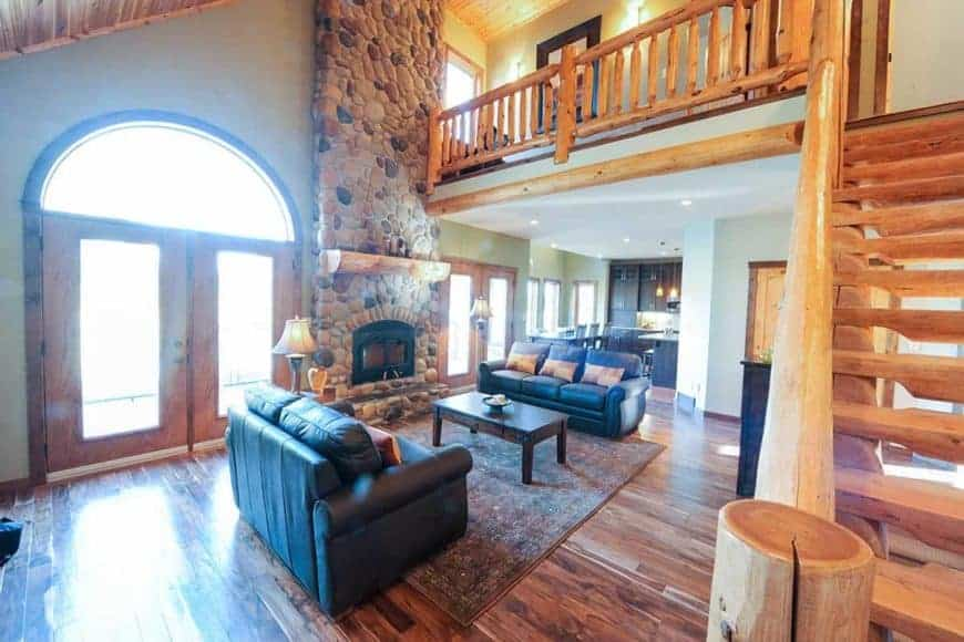 This is the spacious and bright living room with a large stone mosaic fireplace across from the coupleo f black leather sofas flanking a wooden coffee table.
