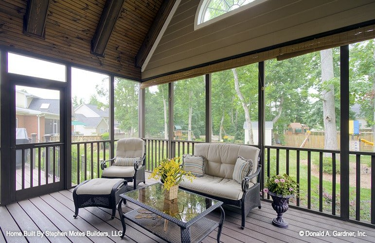 The screened porch is furnished with wicker cushioned seats and a matching glass top coffee table over wide plank flooring.