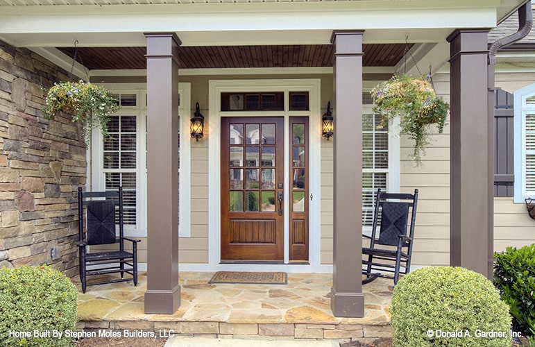 Covered front porch with a black rocker and chair along with a glazed entry door flanked by wall sconces.