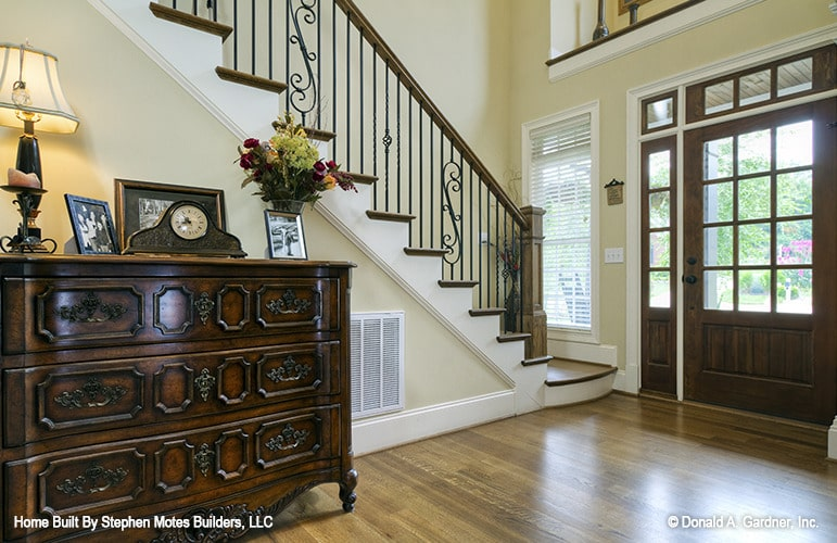 Foyer with an ornate staircase and an antique console table topped with a clock, framed photos, and a table lamp.